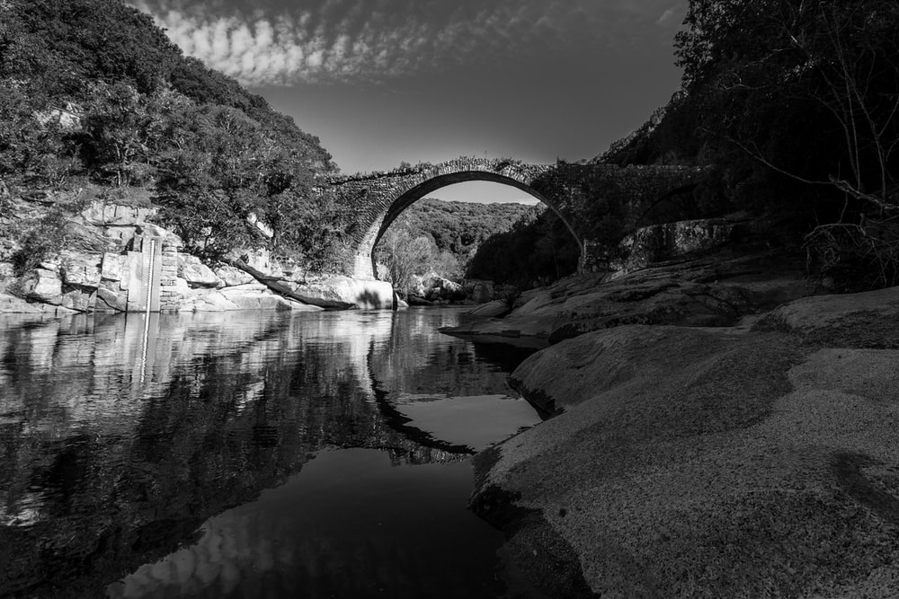 grayscale photography of body of water near the bridge