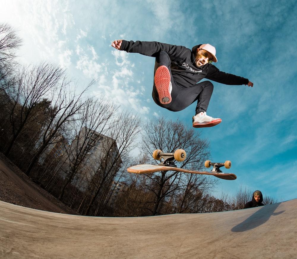 man in black hoodie flipping skateboard during daytime