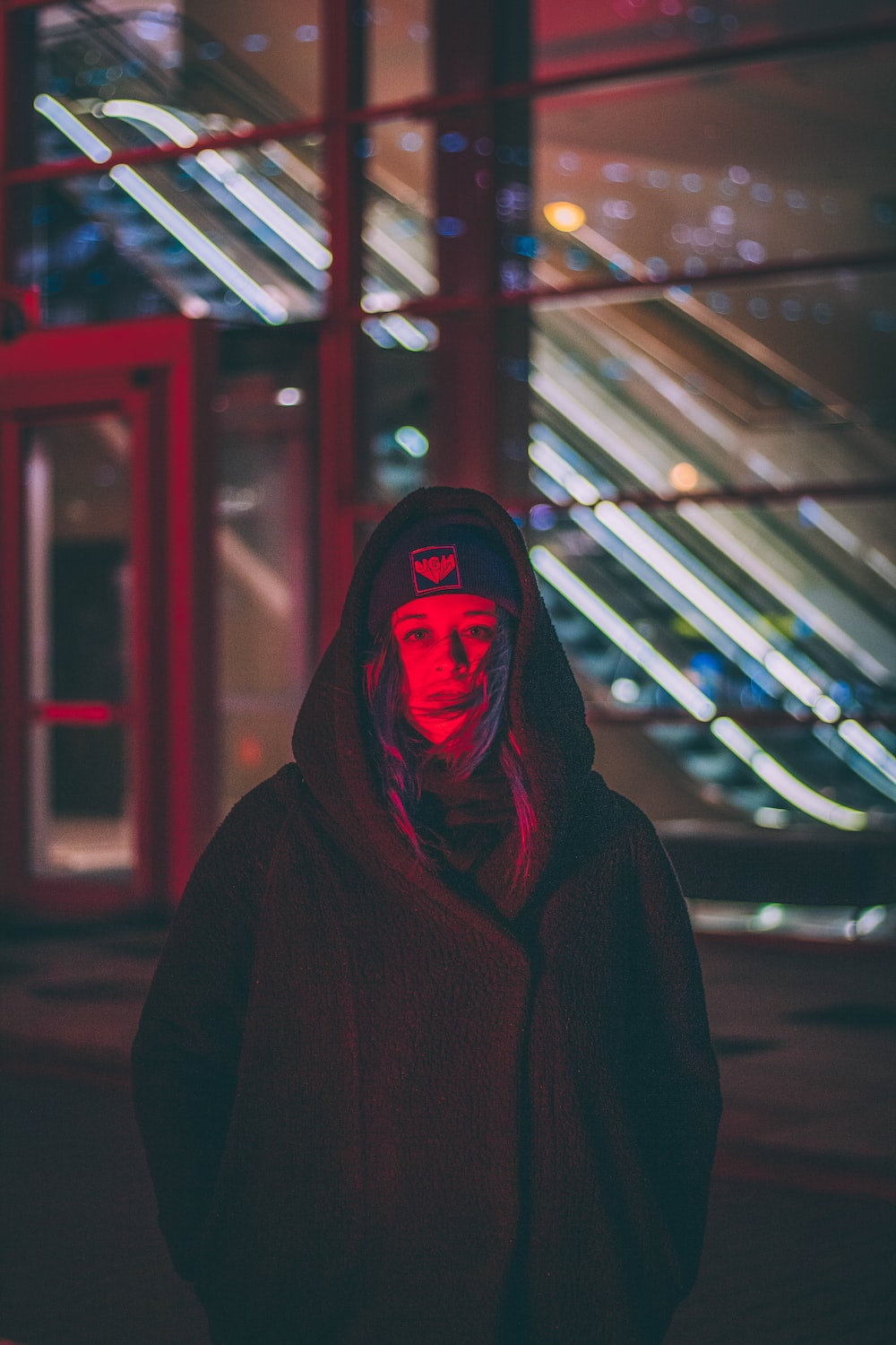 reflection of red light on woman wearing black coat