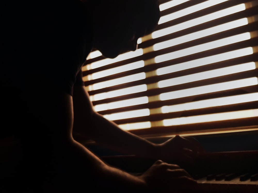 silhouette of person playing piano