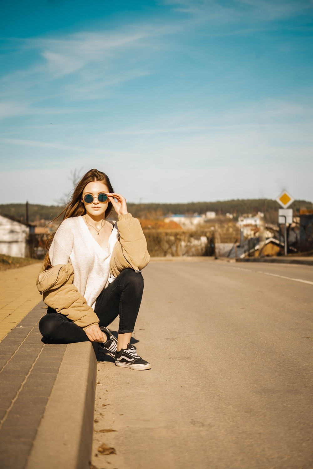 woman holding her sunglasses while sitting near road