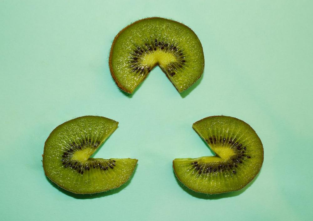 three sliced kiwi fruits forming triangle shape