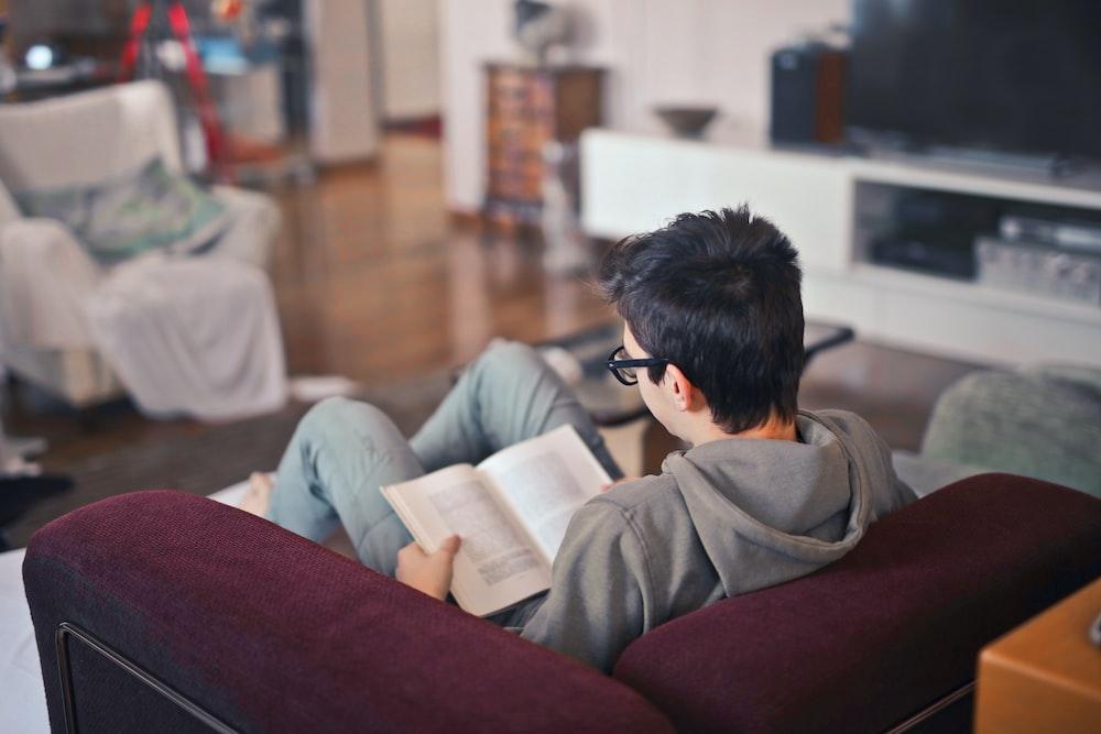man sitting on sofa chair reading book