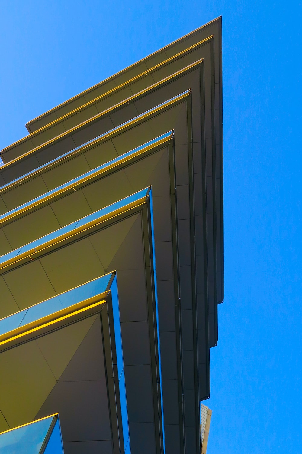 low-angle photography of yellow glass building