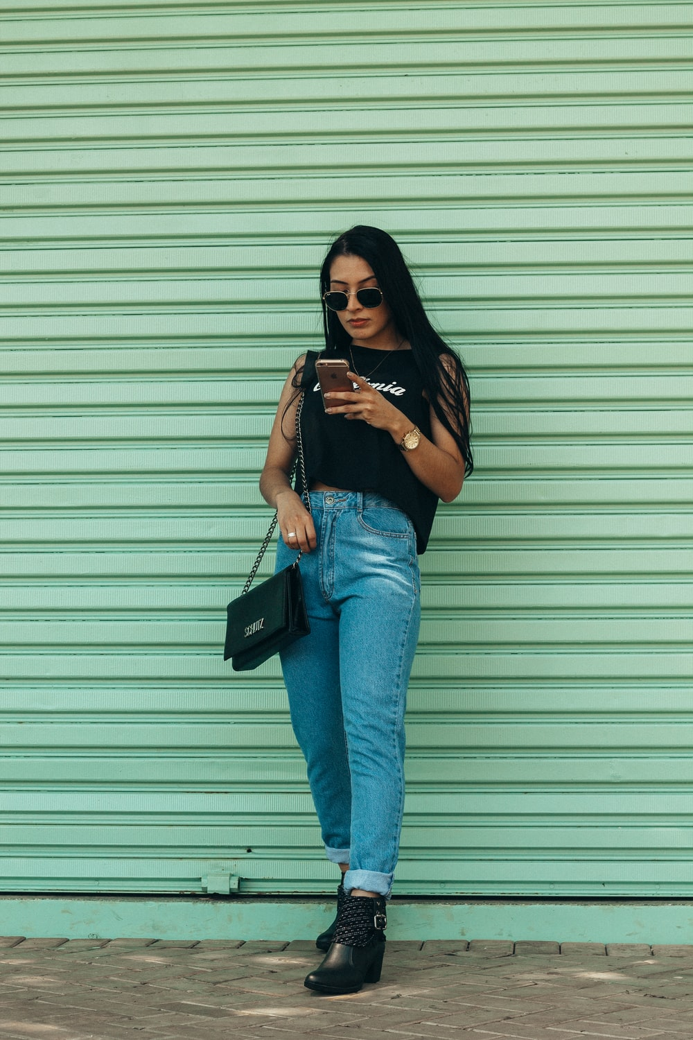 woman in black sleeveless top holding smartphone outdoors