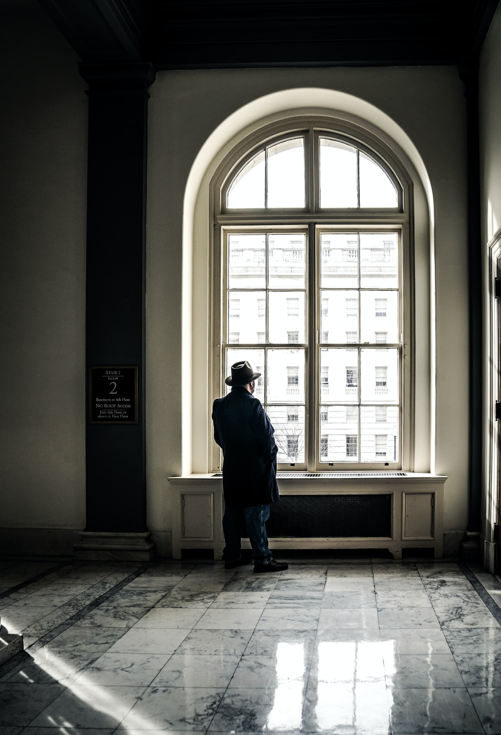 man standing in front of window during daytime