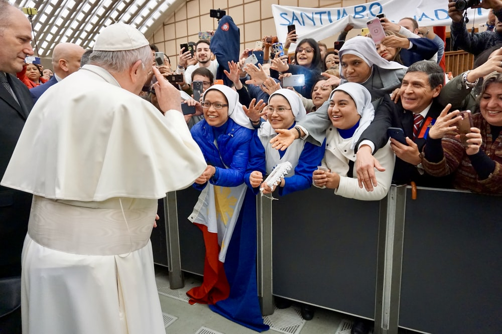 Pope Francis standing surrounded with people