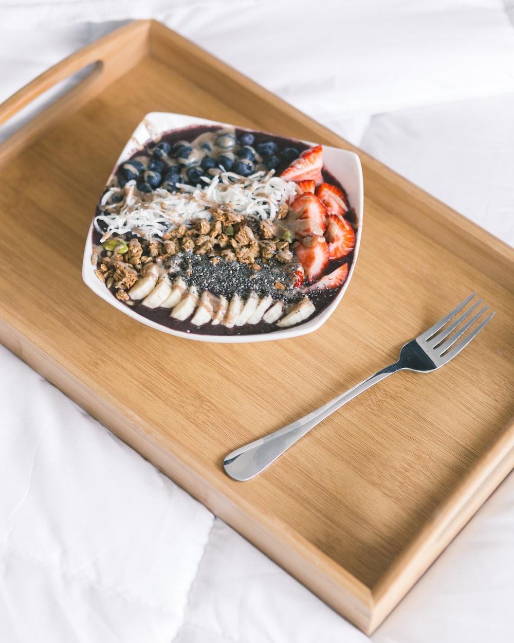 sliced fruit in bowl beside fork on brown serving tray