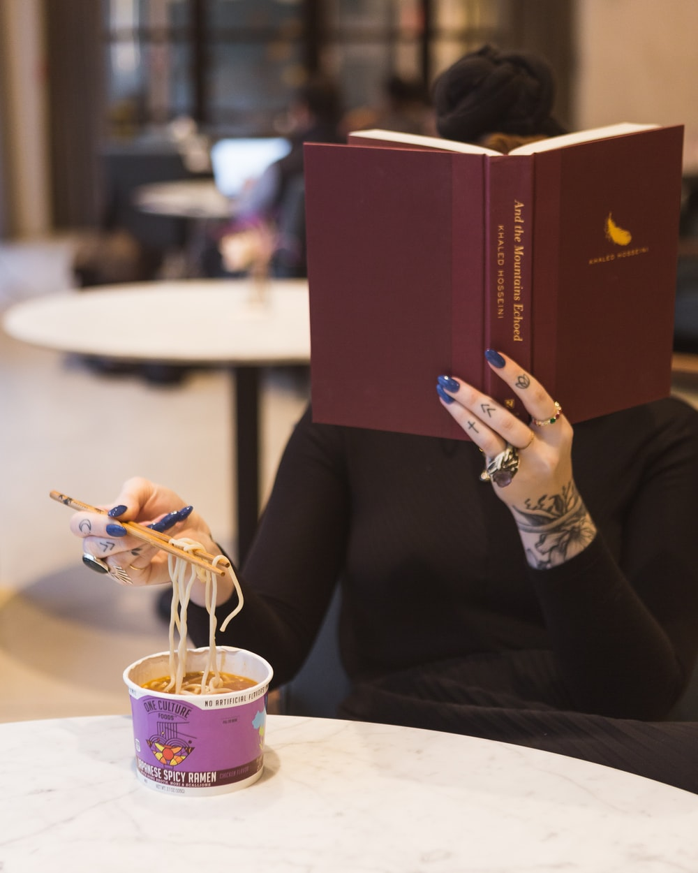 woman sitting by the table reading book while eating noodles