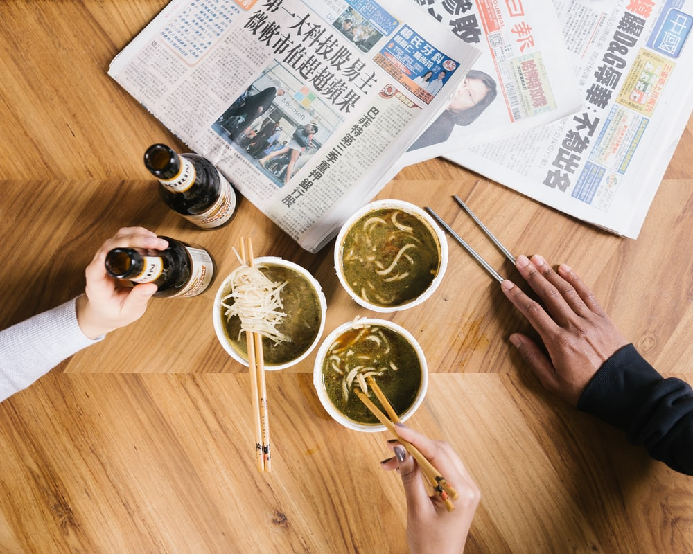 three cup of noodles on table beside newspaper