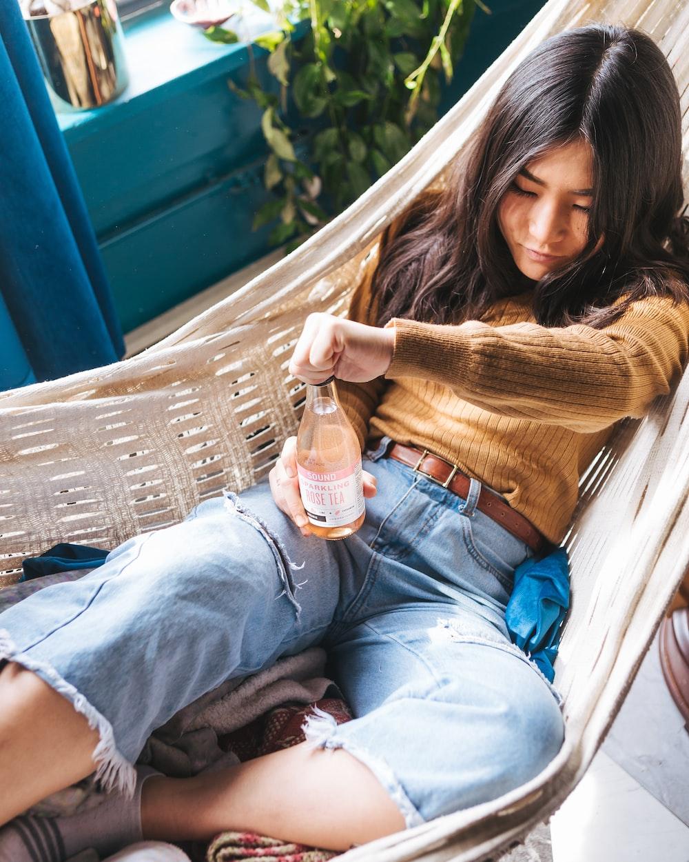 girl's wearing brown sweater on white hammock