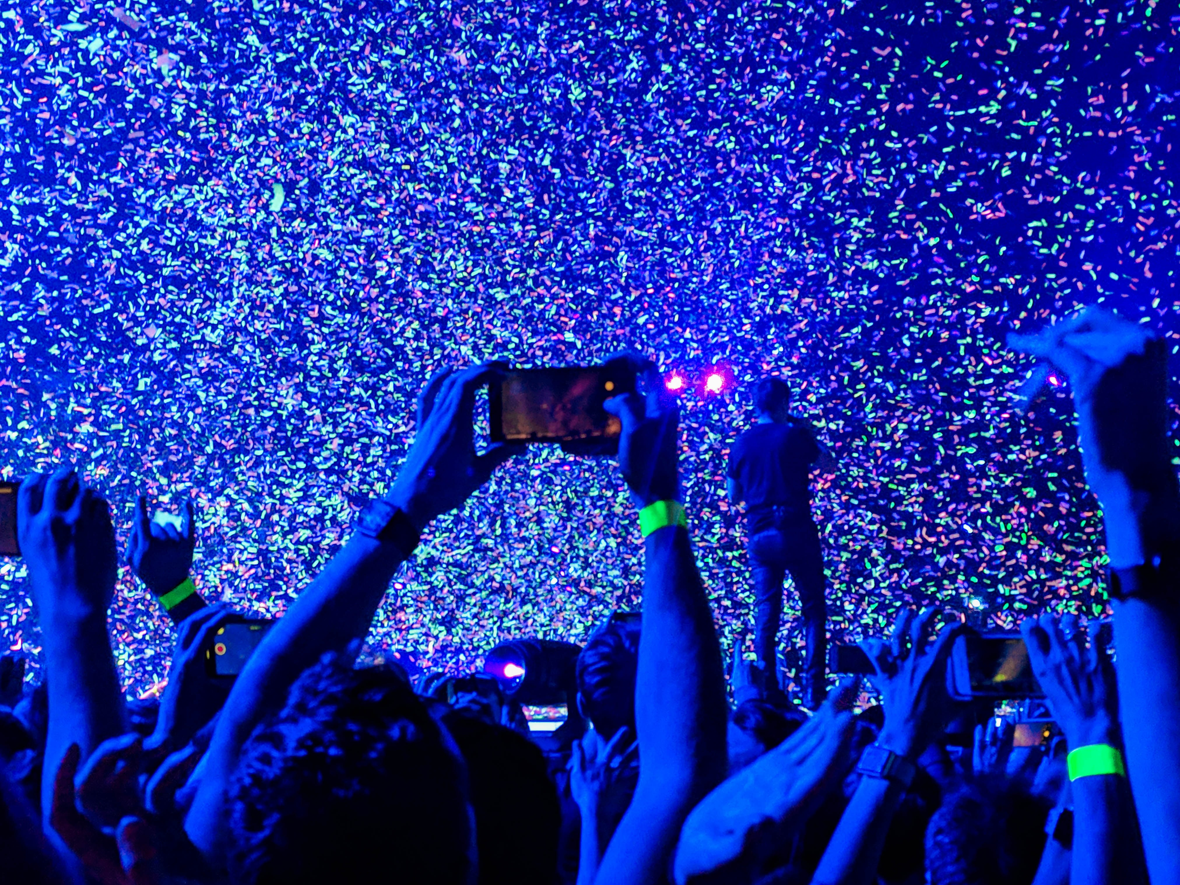 crowd of people taking a picture of person performing on stage