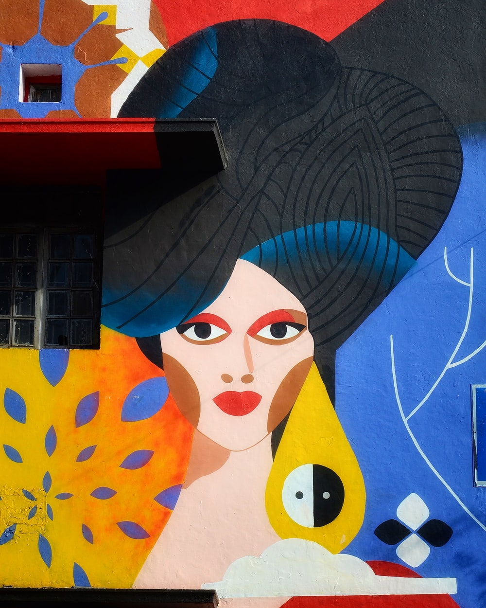 black haired woman painting on wall