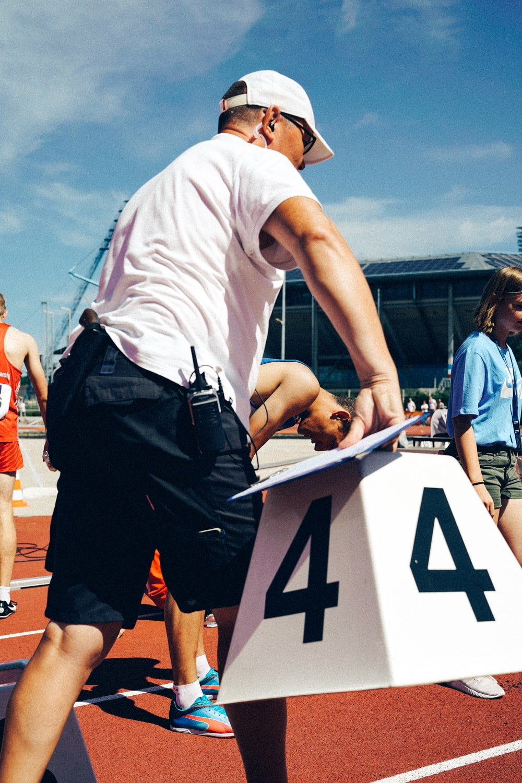 man wearing white shirt on track field