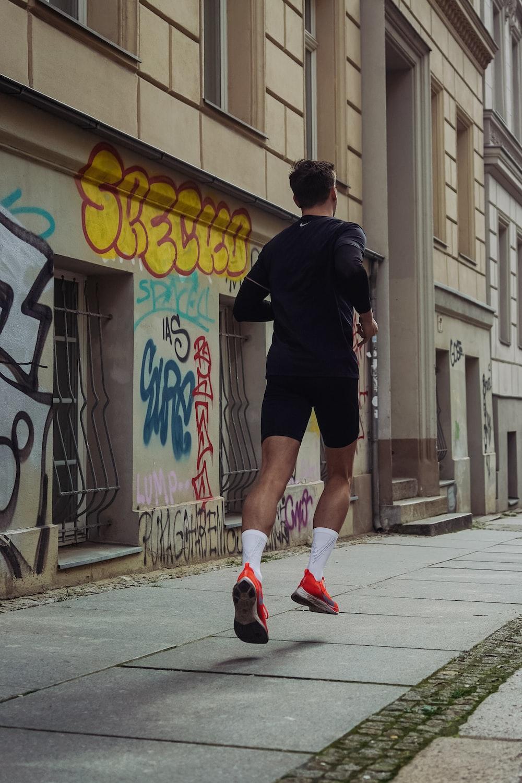 man in black shorts and shirt jogging at sidewalk