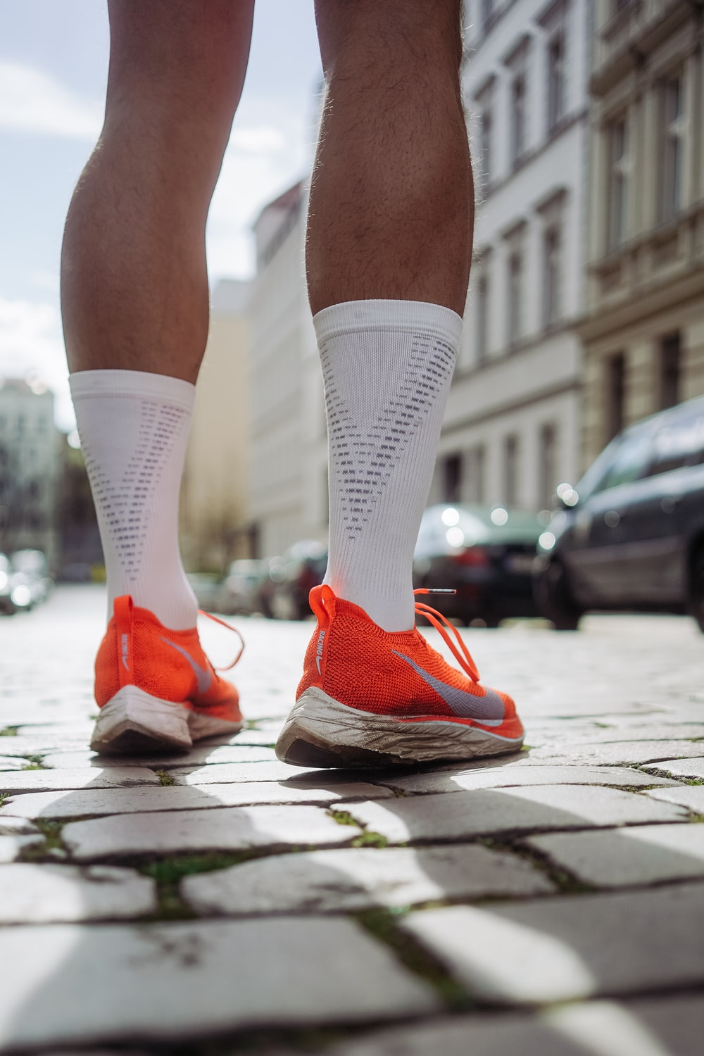 person wearing orange Nike running shoes standing on pavement