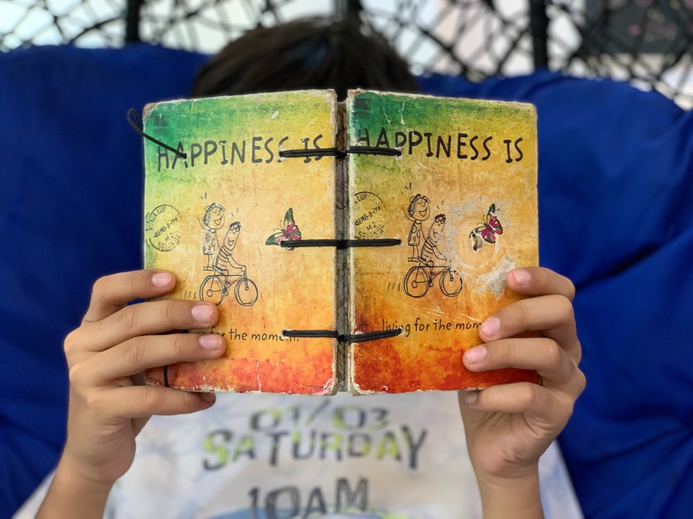 person reading happiness book