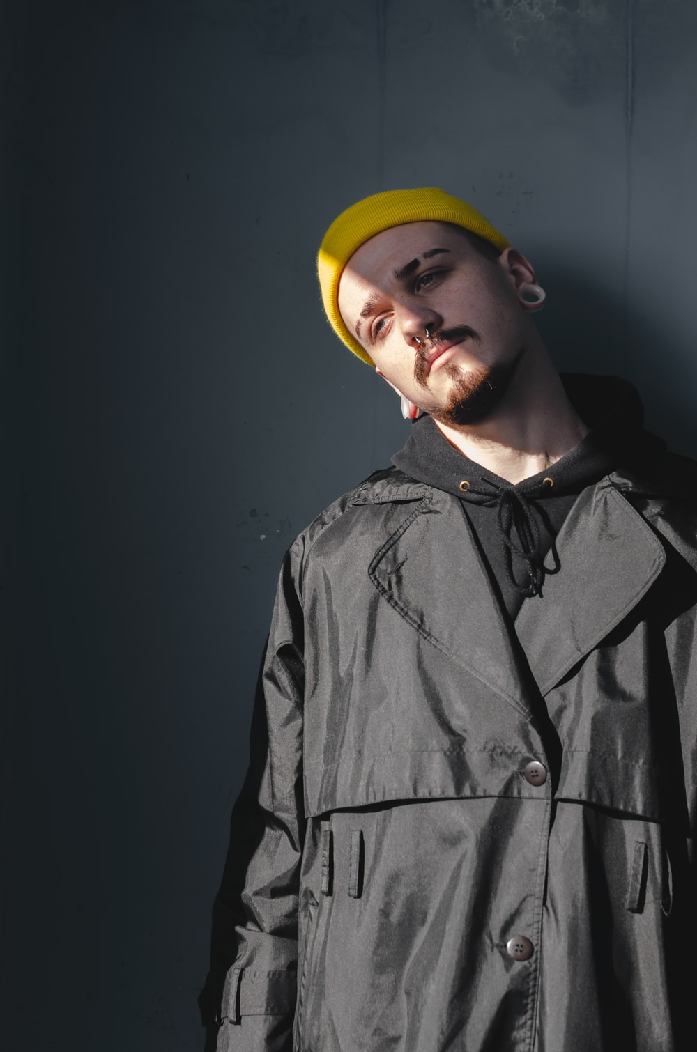 man wearing black coat and yellow beanie leaning on the wall