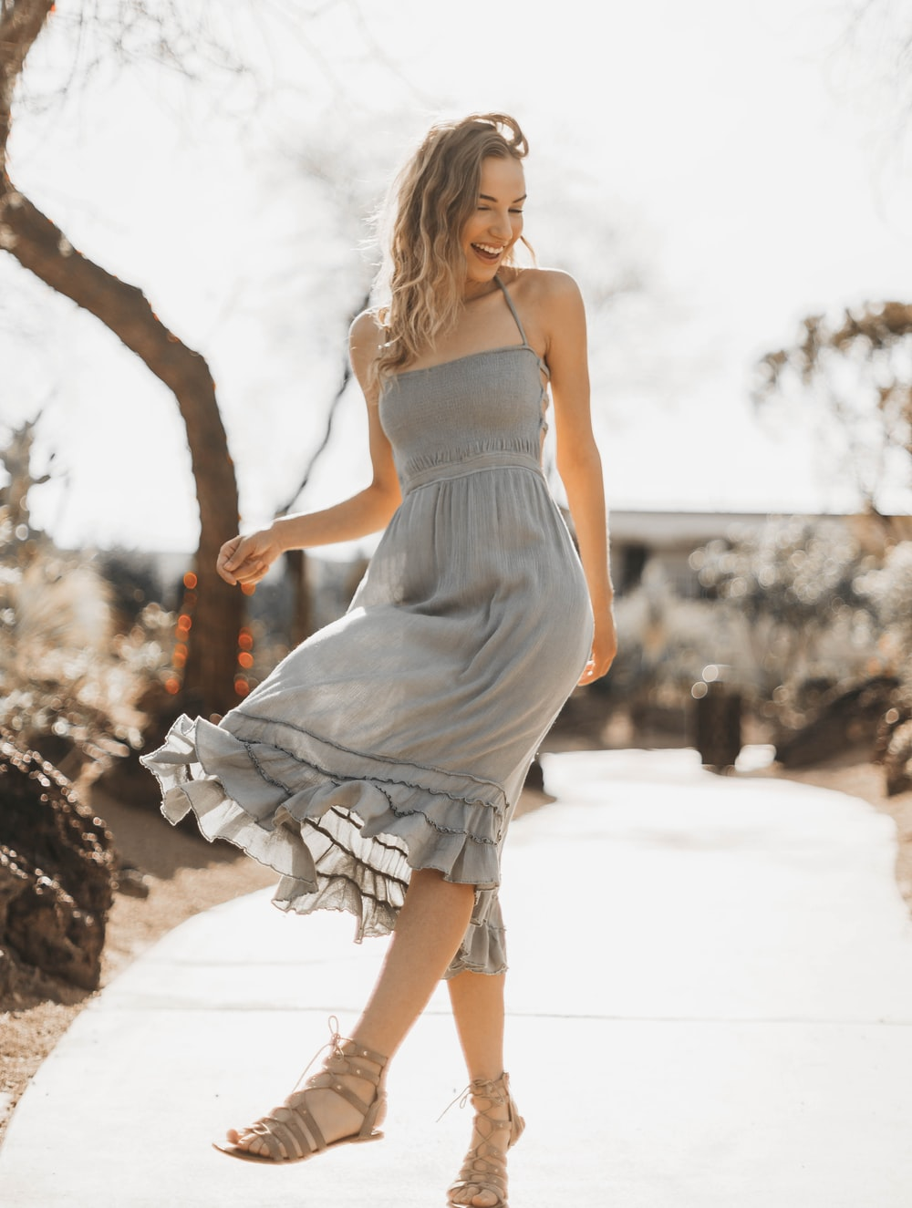 woman in gray spaghetti strap dress standing and smiling