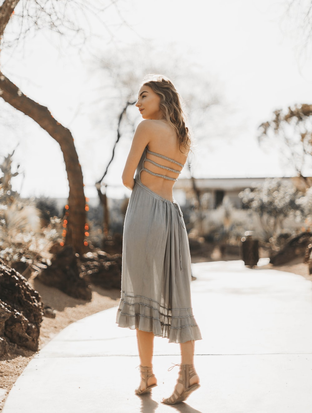 woman wearing gray halter dress standing on pathway