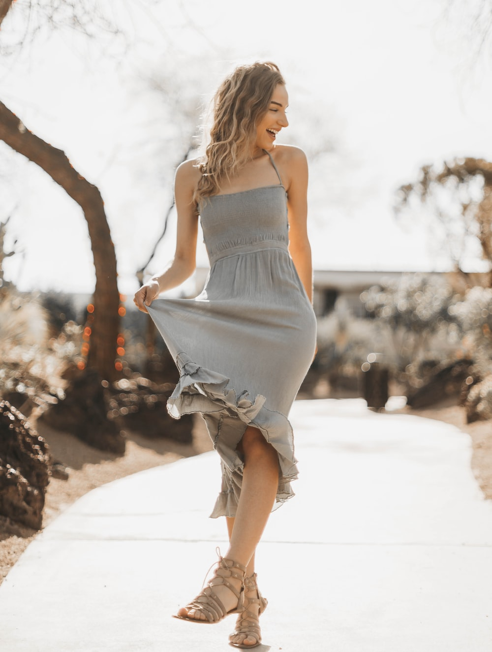 woman in gray dress standing on the pathway