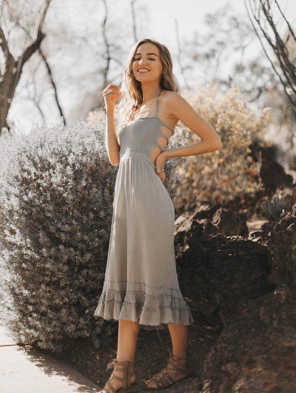 woman wearing grey halter dress standing near bush