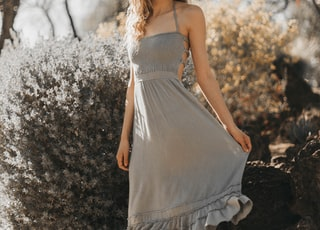 woman in gray spaghetti strap dress standing near flower and smiling