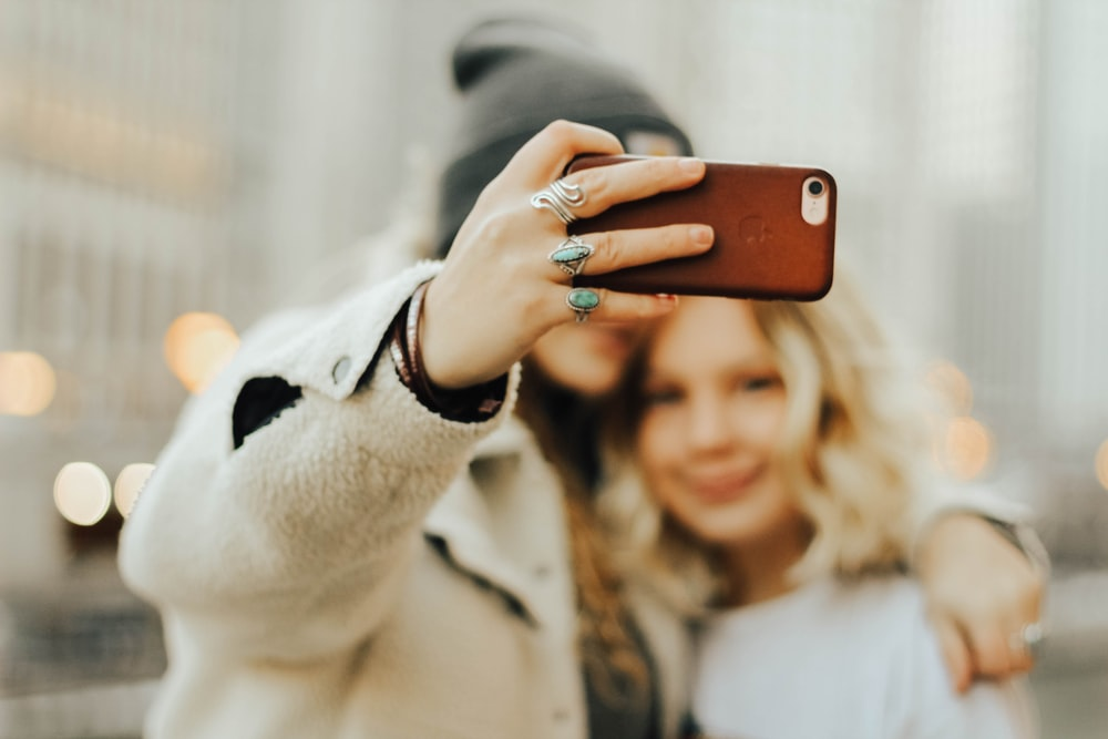 two women taking selfie near building