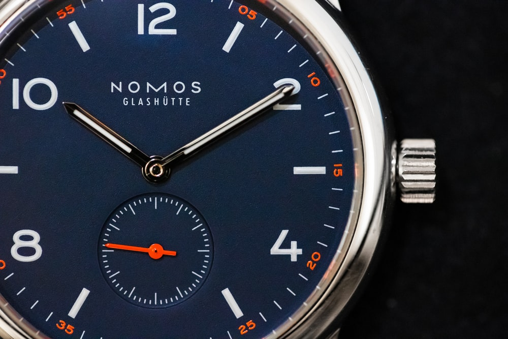 round silver-colored Nomos watch at 10:10