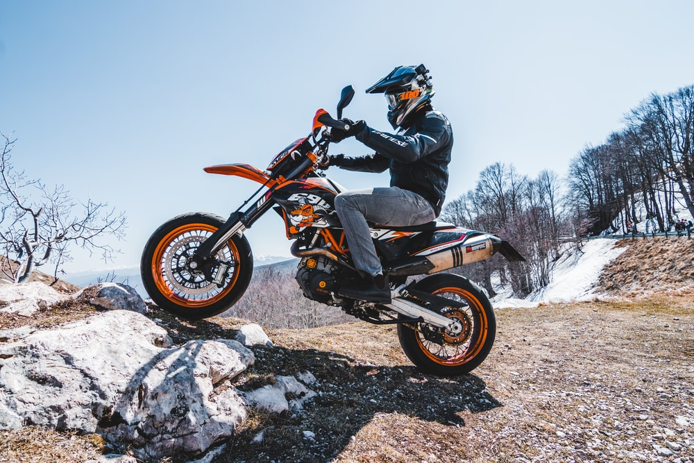 man riding orange and black dirt bike during daytime