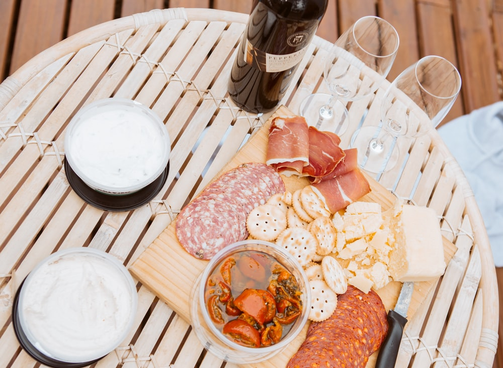 meats and biscuits on tray beside glasses