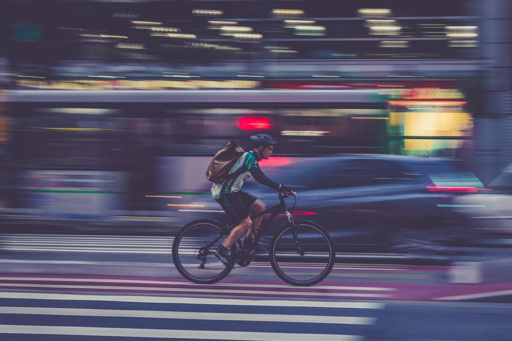 man riding bicycle on road in time lapse photography