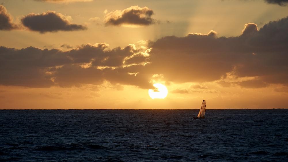 sail boat under orange sky