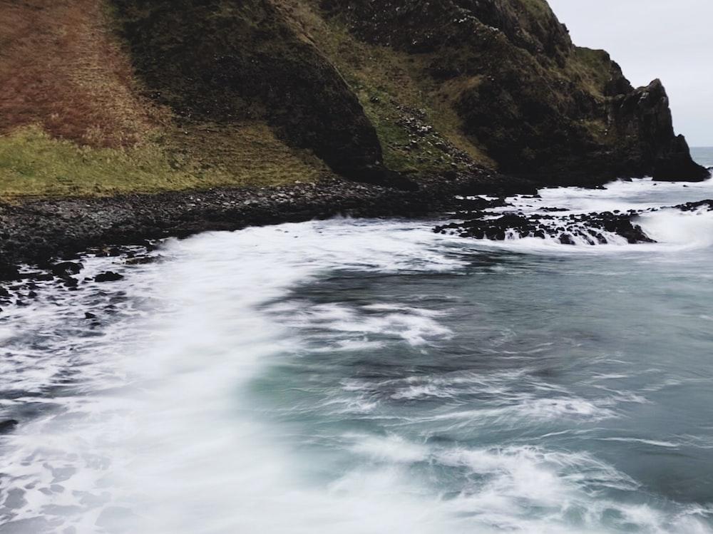 clear blue sea beside rock formation