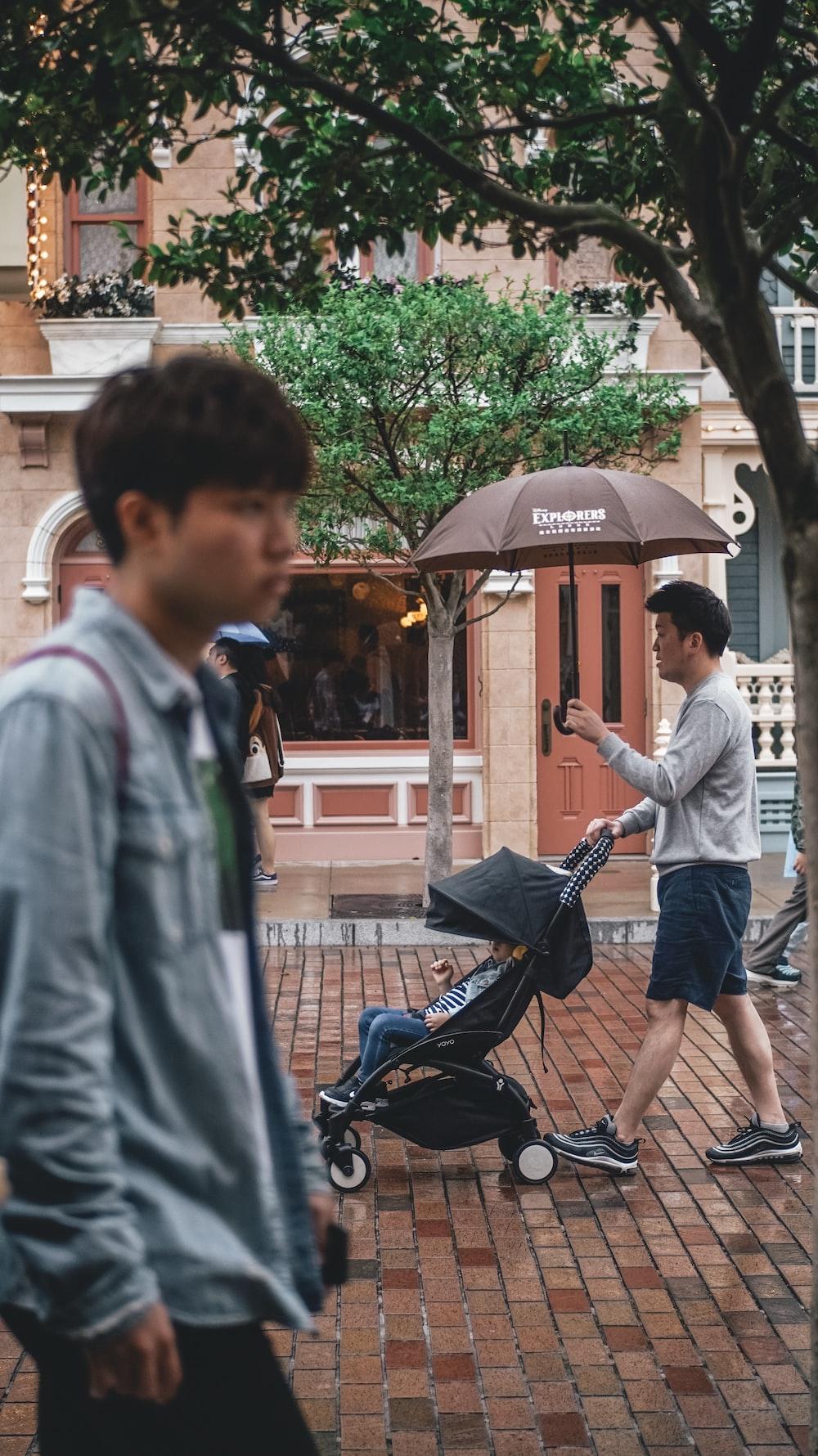 man holding umbrella while pushing stroller