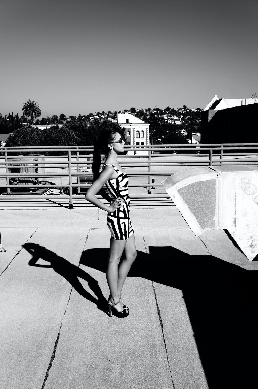 woman wearing skirt standing near railings