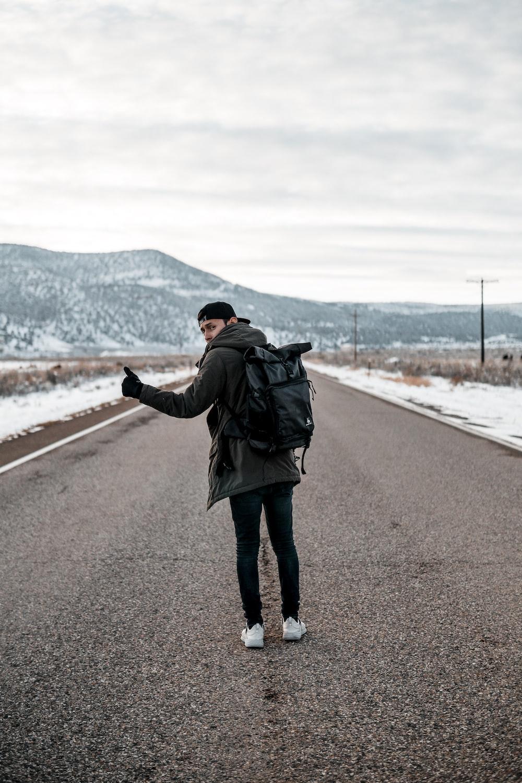 man standing on asphalt road
