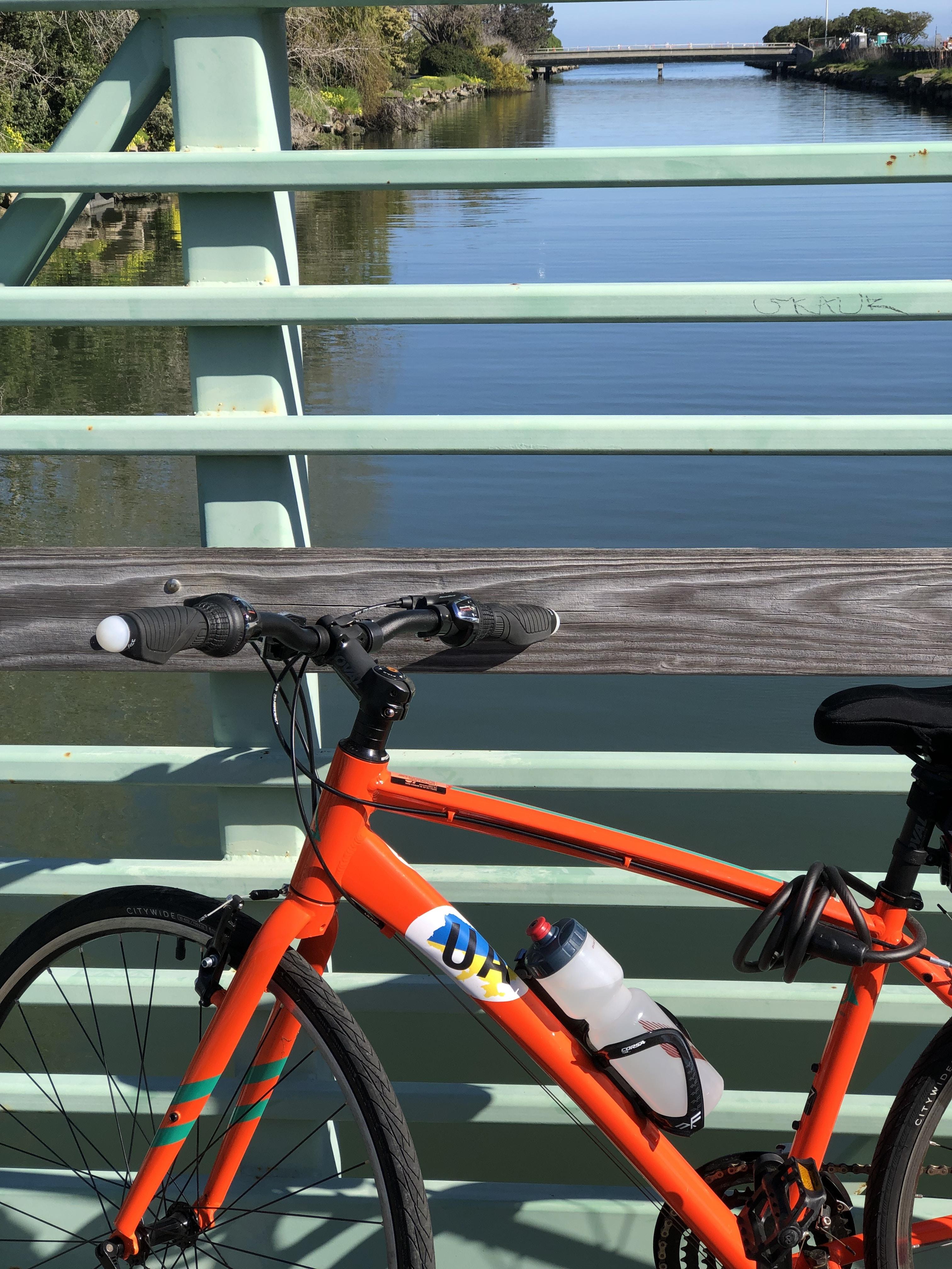 orange rigid bike on bridge