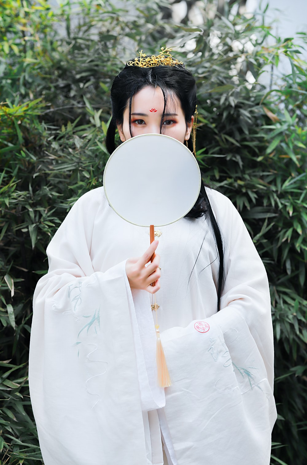 woman wearing kimono costume standing and covering her face using handfan