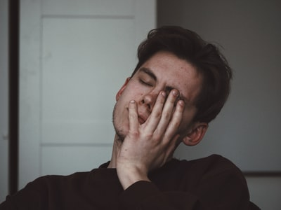 man wearing black crew-neck top tired zoom background