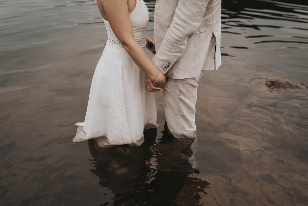 two person standing on body of water