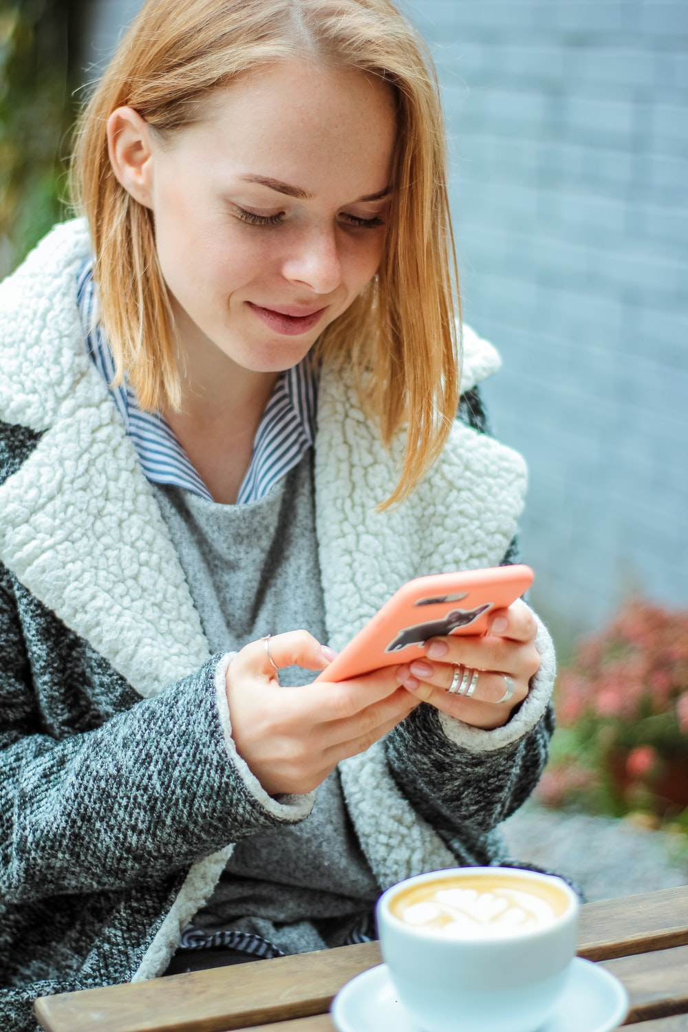 woman smiling while using her phone