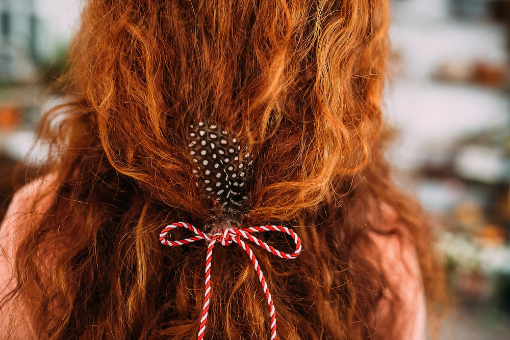 person with red and white bow hair tie on hair
