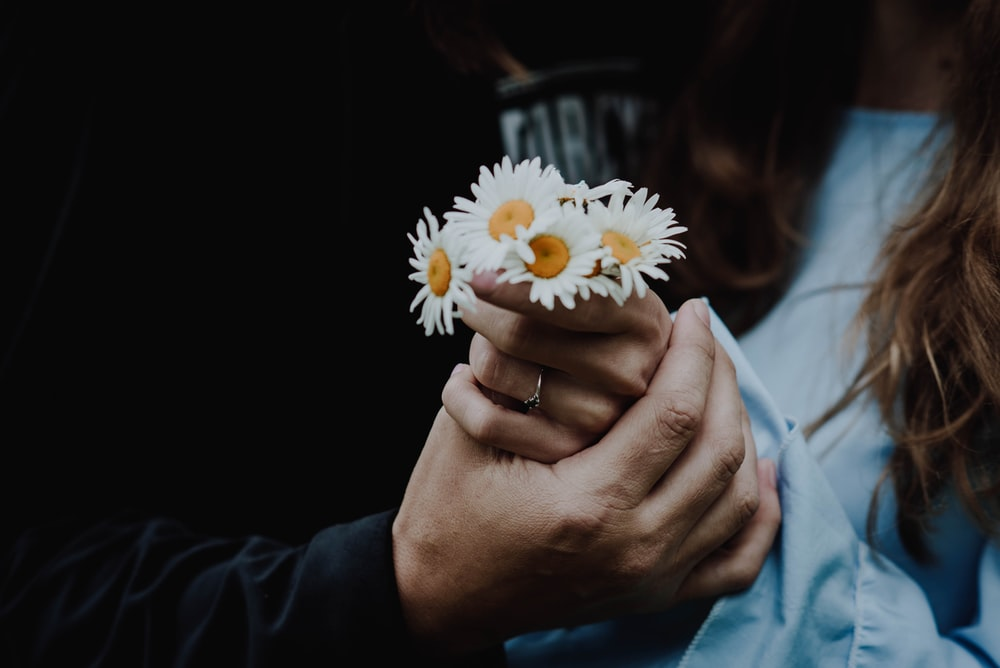low-light photo of man holding the hand of woman holding white daisies