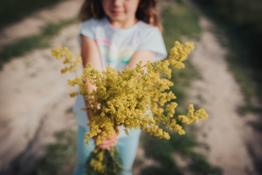 girl holding yellow flower bouquet