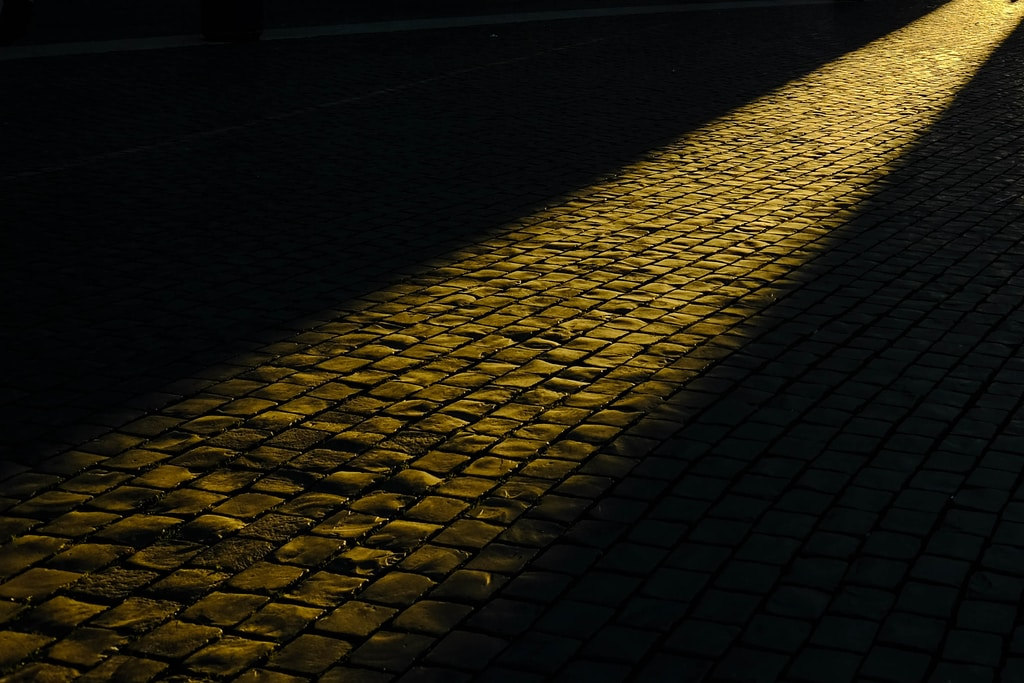 Observing light beaming on the path of cobblestone in Rome.