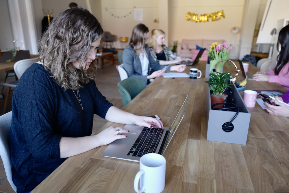 woman using MacBook in room