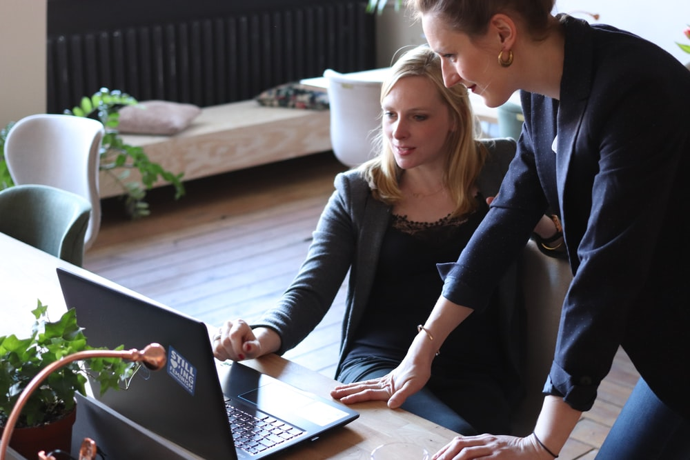 two woman looking at laptop screen