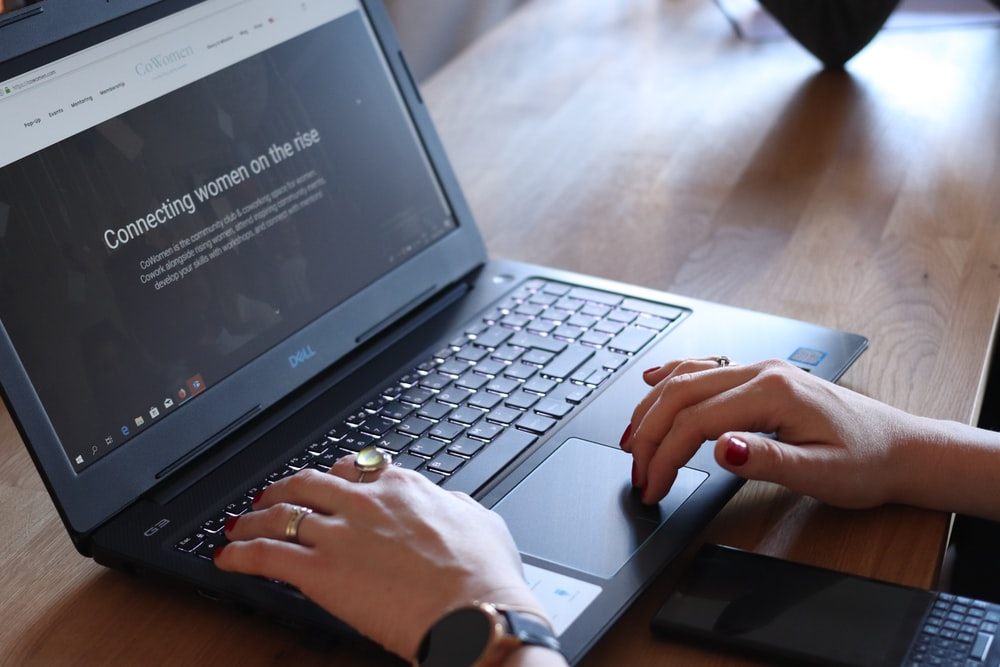 person using Dell laptop in room