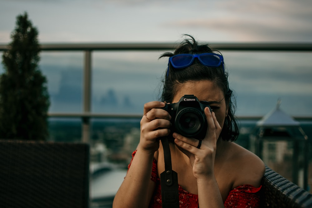 woman taking picture using a DSLR camera